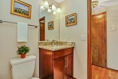 Small guest Bathroom with wood vanity and open door to hallway.  stock photos