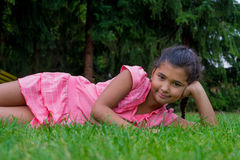 Small gypsy child girl lay aside in grass smiling happy clothed Royalty Free Stock Photography