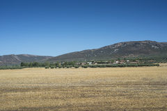 Small hamlet in La Mancha, Spain. Small hamlet in an agricultural landscape in La Mancha, Ciudad Real Province, Spain. In the background can be seen the Toledo Stock Image