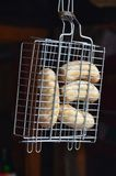 A small hand grill is filled with fried thick sausages on a dark background.  royalty free stock photos