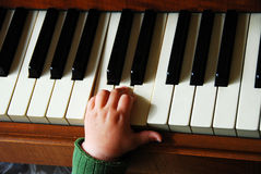 Small hand on piano. A toddler places his hand on piano keys Stock Images