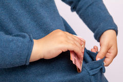 Small hand puts ten euro banknote in pocket Royalty Free Stock Photography