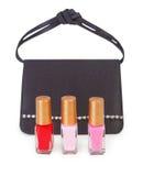 Small handbag and vials of nail polish Royalty Free Stock Photos