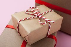 Small handmade gift boxes with a red ribbon on a pink background royalty free stock photo