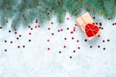 Christmas gift on the background of Christmas tree branches decorated with hearts royalty free stock image