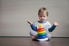 A small child has gathered a bright children`s pyramid and is happy. royalty free stock images