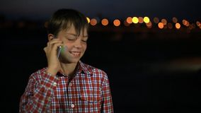 Small handsome boy 8 years old, talking on mobile phone at night in the city. The boy speaks smartphone smiling happy. Small handsome boy 8 years old, talking on stock video footage