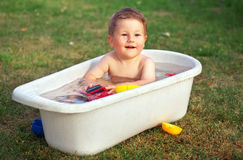 A small happy baby bathed in the bath and playing Royalty Free Stock Photos