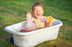 A small happy baby bathed in the bath and playing Stock Images