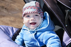 Small happy baby in blue overalls in stroller Stock Image