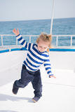Small happy baby boy dancing on yacht in marine shirt Royalty Free Stock Images