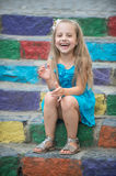 Small happy baby girl in blue dress on colorful stairs Stock Image