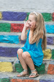 Small happy baby girl in blue dress on colorful stairs. Small happy baby girl or cute child with adorable smiling face and bow in blonde hair in blue dress Royalty Free Stock Image