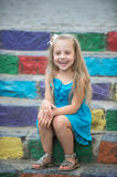 Small happy baby girl in blue dress on colorful stairs. Small happy baby girl or cute child with adorable smiling face and bow in blonde hair in blue dress stock photo