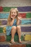 Small happy baby girl in blue dress on colorful stairs. Small happy baby girl or cute child with adorable smiling face and bow in blonde hair in blue dress stock image