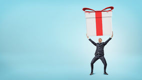 A small happy businessman standing on blue background and holding a giant gift box with both hands. Stock Photo