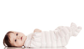 Small happy child, isolatrd on white. Cute baby lying on your back on white floor background and smiling big Stock Image