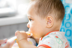 Small happy child sitting in a chair and eats yogurt from whose face is marred in baby food Royalty Free Stock Images