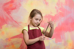 Small happy girl chef in cook apron holding cooking tool Royalty Free Stock Photos