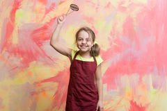 Small happy girl chef in cook apron holding cooking tool Stock Photos