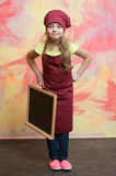Small happy girl chef in hat, apron with blackboard Stock Images