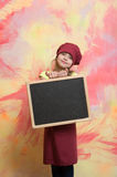 Small happy girl chef in hat, apron with blackboard Stock Image