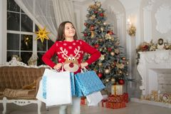 Small happy girl at christmas. Christmas. Kid enjoy the holiday. Happy new year. girl with shopping bags. morning before. Xmas. New year holiday. little child royalty free stock image