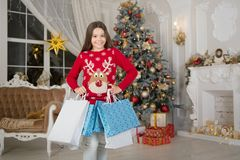 Small happy girl at christmas. Christmas. Kid enjoy the holiday. The morning before Xmas. girl with shopping bags. New. Year holiday. little child girl likes stock photos