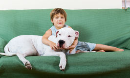 Small happy girl on couch with dog Stock Photo