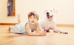 Small happy girl on the floor with dog Royalty Free Stock Photos