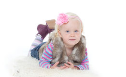 Small happy girl in a fur vest. On a white background. Studio shooting Stock Photo