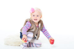 Small happy girl in a fur vest Stock Image