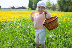 Small happy girl standing on meadow with basket Royalty Free Stock Images