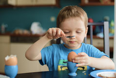 Small happy three year old boy breaks the egg. On breakfast royalty free stock image