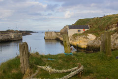 The small harbor at Ballintoy on the North Antrim Coast of Northern Ireland with its stone built boathouse on a day in spring Royalty Free Stock Photos