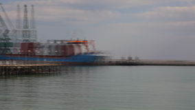 Small harbor panning to industrial ship,editorial stock video footage