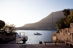 small harbor at sunset on the Como lake with a touring boat Sulo background and two people behind embracing stock images