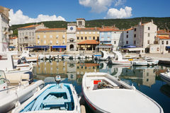 Small harbour with boats. Small harbor with fishing boats. Reflections of boats and houses in the sea. In the back, traditional houses and clear blue sky. Town Royalty Free Stock Photos