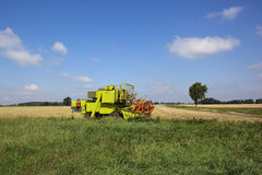 Small harvester. A small green harvester on the edge of a stubble field in late summer under a blue sky Stock Photography