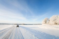 Small hatchback car driving along a snowy, icy road on a beautiful, cold and sunny winters day. Small white hatchback car driving along a snowy winter road on a Royalty Free Stock Image