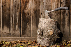 Small hatchet in log in front of wooden fence Royalty Free Stock Photography