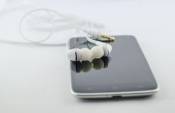 Small headphones with mobile phone Stock Image