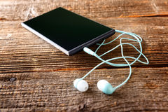 Small headphones with mobile phone Stock Photography