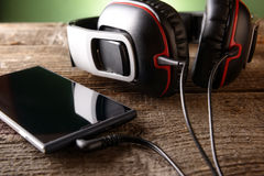 Small headphones with mobile phone Royalty Free Stock Photo