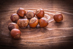 Small heap of hazelnuts on vintage wooden board Stock Photos