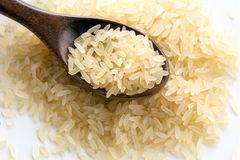 Small heap of parboiled rice with a wooden spoon on white, close Royalty Free Stock Photo