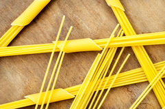Small heap of penne and spaghetti wooden table. Small heap of penne and spaghetti on a wooden table Stock Images