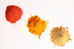 Small heap of spices, Red Chilli Powder, Yellow tu. On a white background, Diagonal shot of a small heaps of turmeric powder (in centre), coriander powder (on Stock Photos