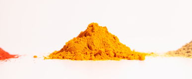 Small heap of spices, the turmeric powder, coriander powder and red chilli powder. On a white background, Horizontal shot of yellow turmeric powder. coriander Stock Images