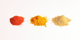 Small heap of spices, the turmeric powder, coriander powder and red chilli powder. On a white background, Horizontal shot of yellow turmeric powder. coriander Royalty Free Stock Photo